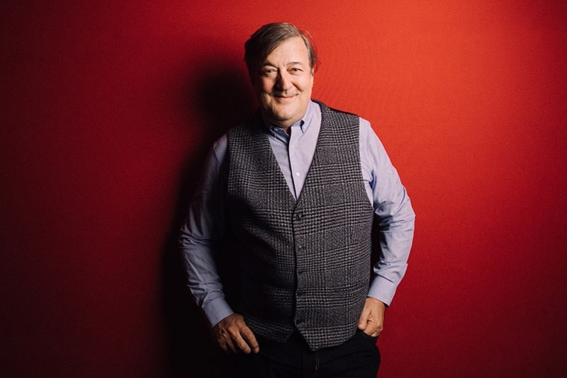 Stephen Fry against red background